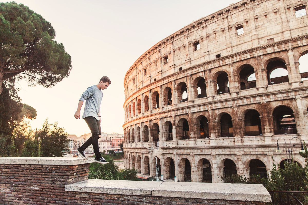 a man walking by an ancient roman site in rome, italy