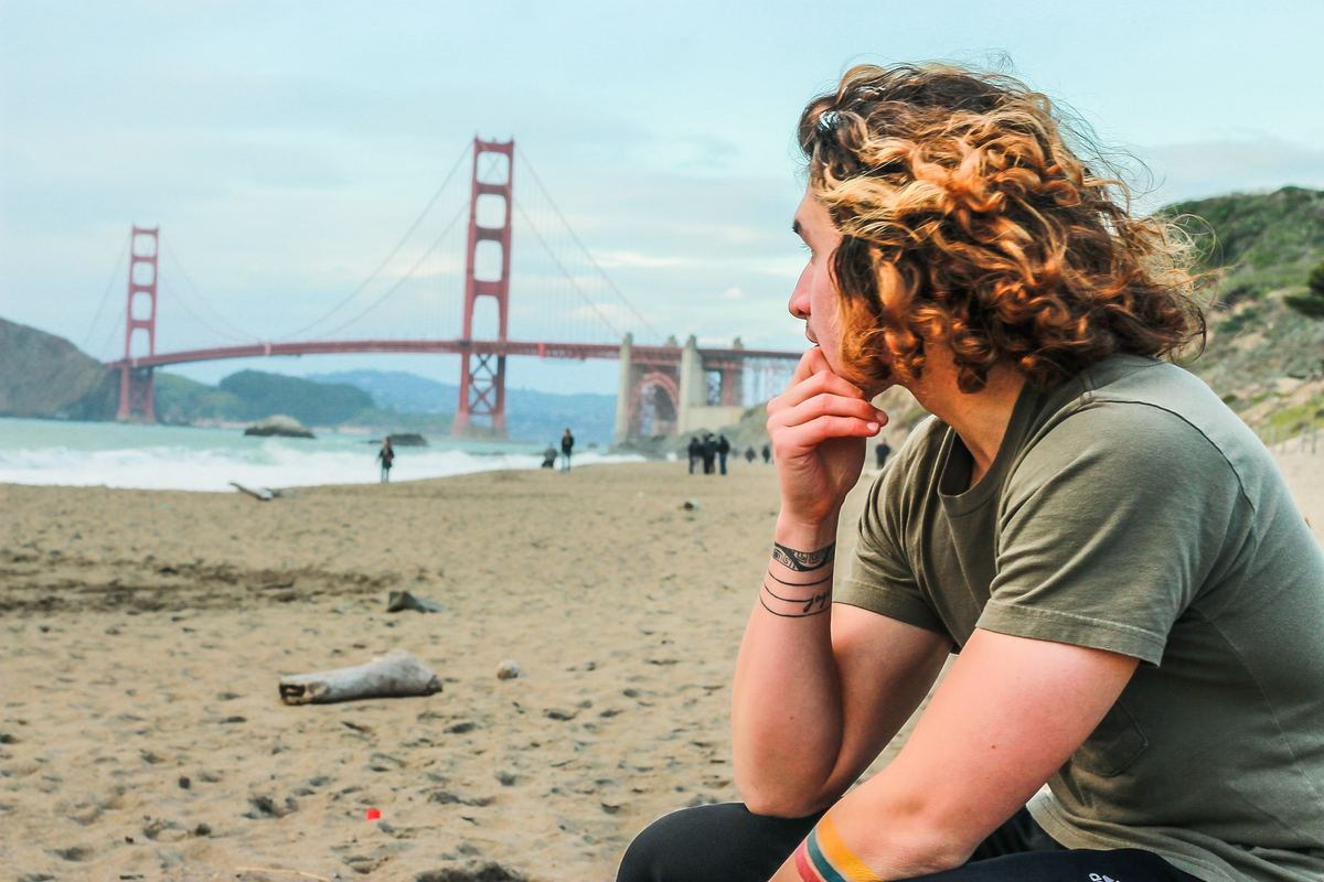 a man sitting on the beach looking at the golden gate bridge in san francisco