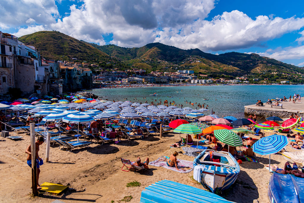 tourists with umbrellas on a beach in sicily, italy
