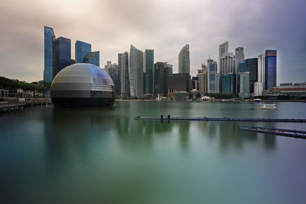 a floating glass orb in the marina in front of the singapore skyline