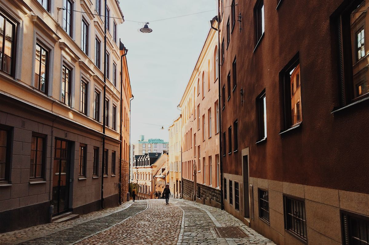 a far away shot of a person walking in between buildings in stockholm, sweden