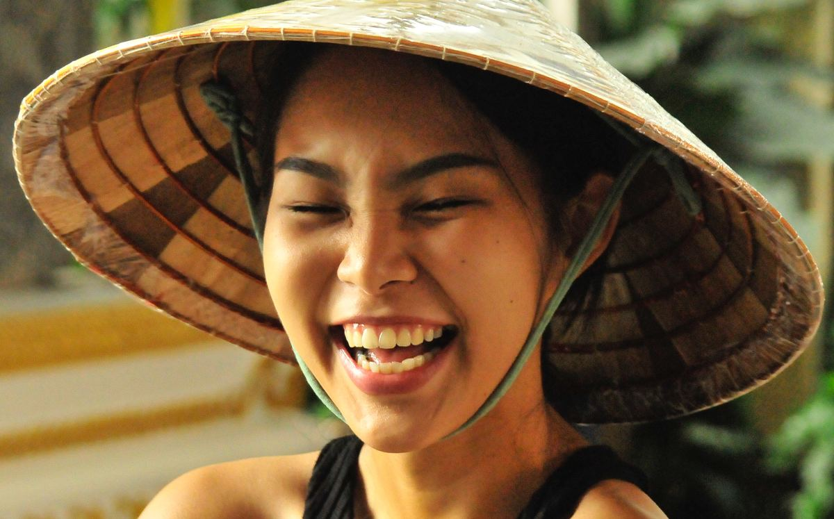 a woman wearing a tradiional thai hat smiling in thailand