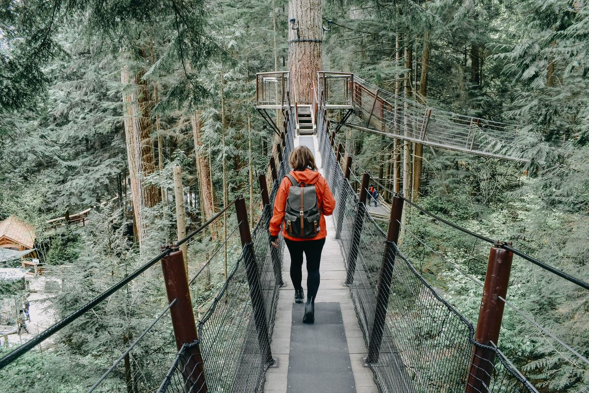 a woman walking on a bridge in vancouver