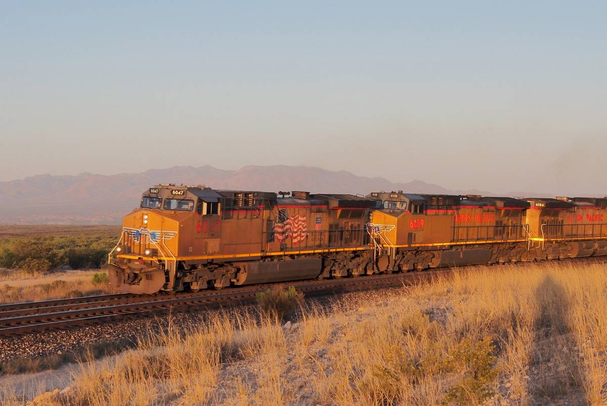 The train Sunset Limited drives through the desert during sunset in Arizona.