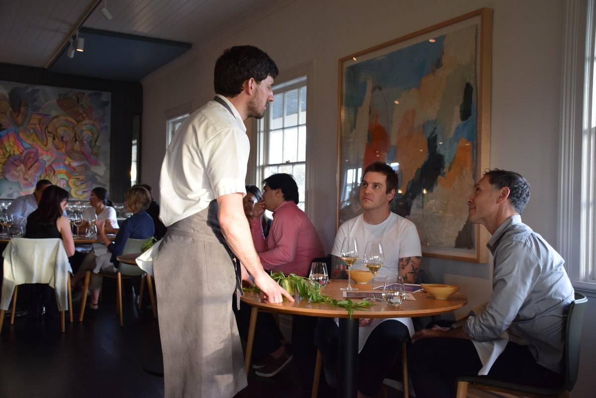 A waiter attends to guests at the restaurant Brae, Victoria.