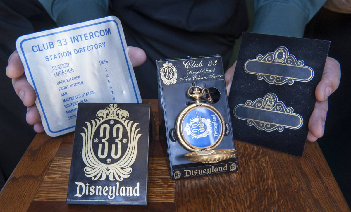 A Club 33 member displays the exclusive merchandise that only members receive.
