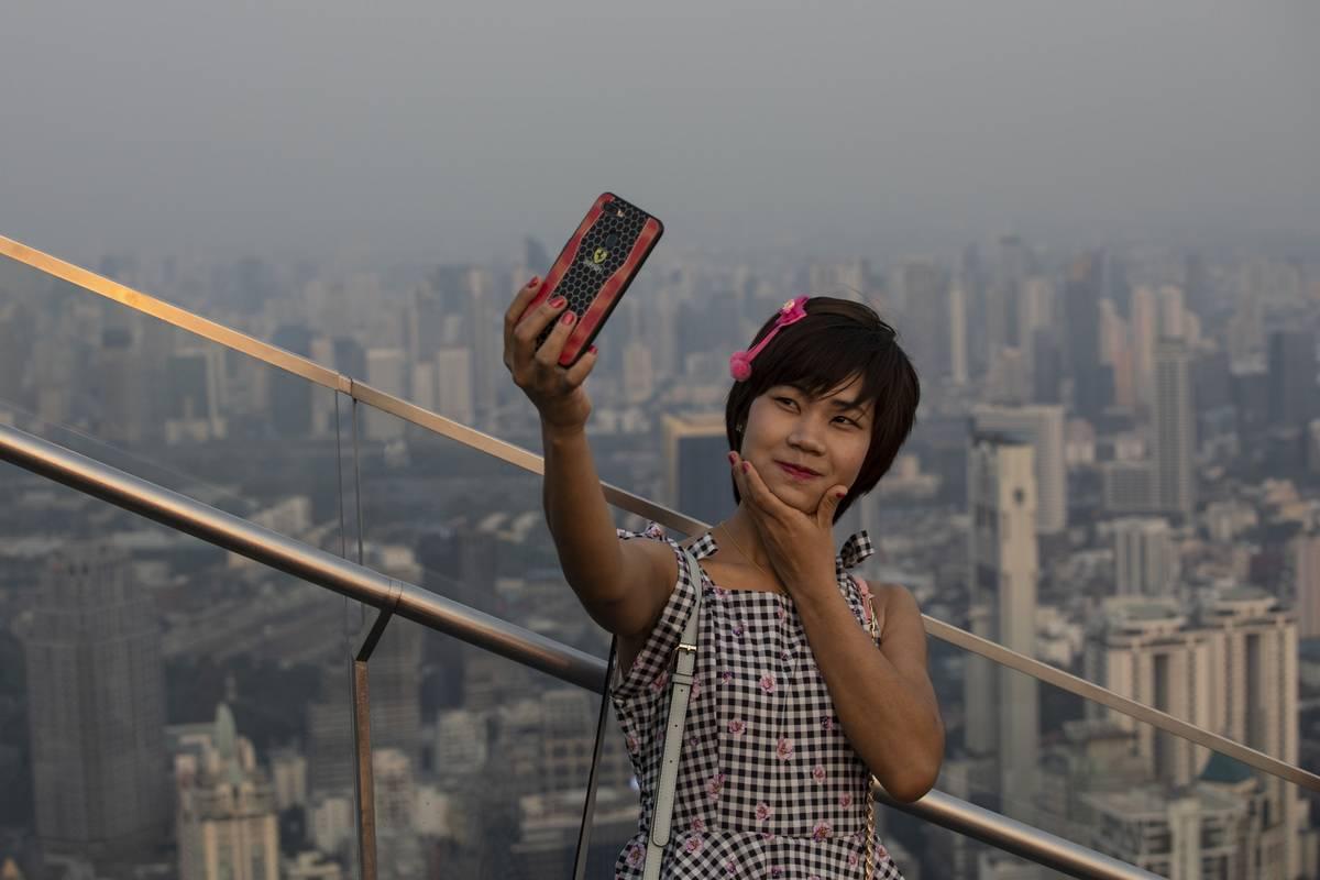 A tourist takes a selfie in Bangkok.