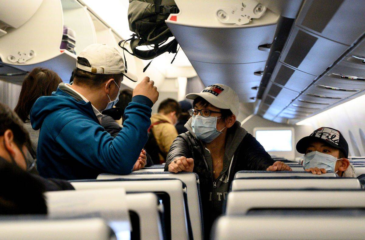 Passengers wear protective face masks on a plane.
