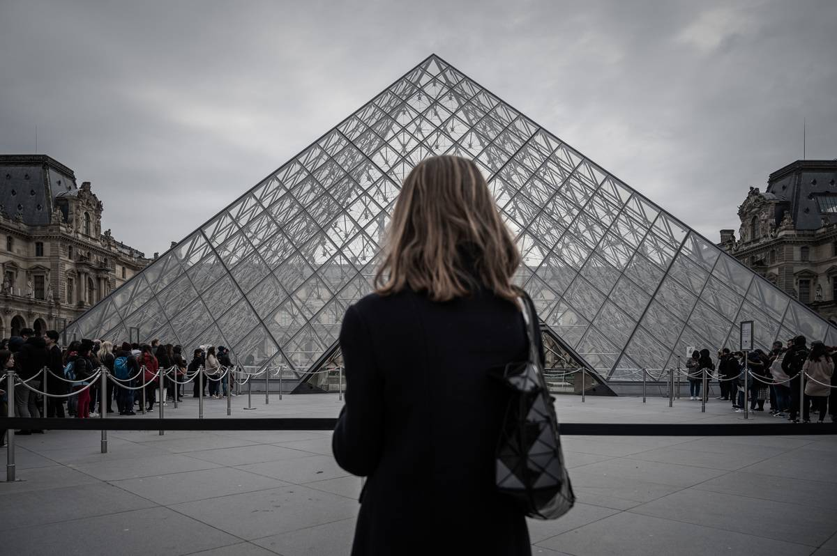 A woman stands in front of the pyramid of the newly opened Louvre museum, which closed temporarily from coronavirus.