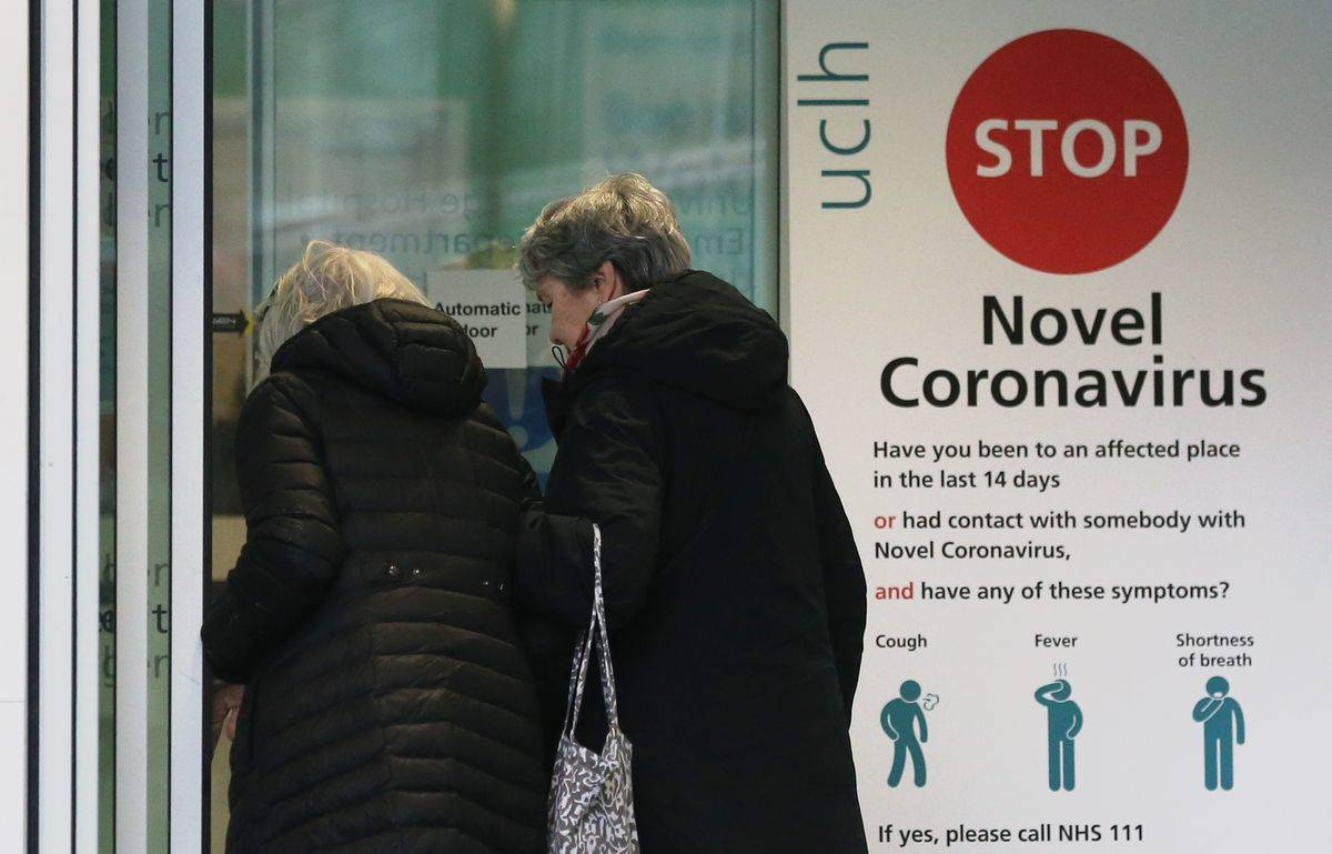 Two women walk past a sign providing guidance information about novel coronavirus (COVID-19) at the entrance to University College Hospital.