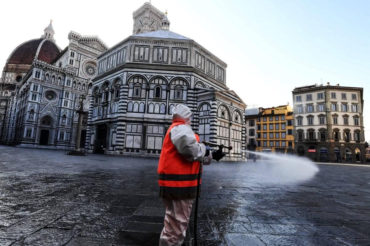 An employee of the municipal company disinfects Piazza del Duomo, in Florence