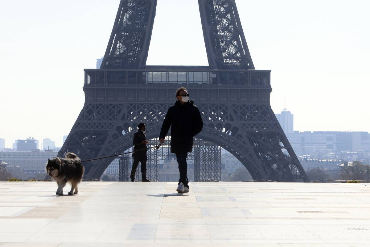 A man walks his dog at Trocadero place a front the Eiffel Tower deserted due to coronavirus outbreak, in Paris, France