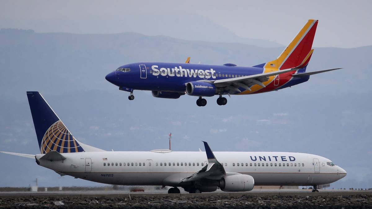 A Southwest Airlines plane lands next to a United Airlines plane at San Francisco International Airport