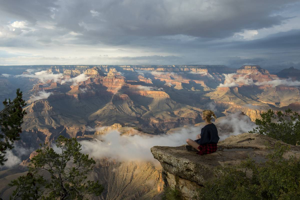 A young woman is sitting on a rock near Yavapai Point on the South Rim overlooking the Grand Canyon