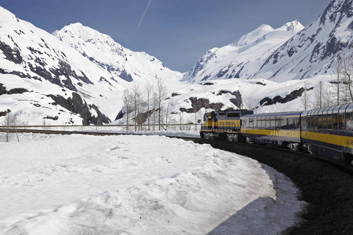 A train on the Summit Express in Alaska passes snowy mountains.