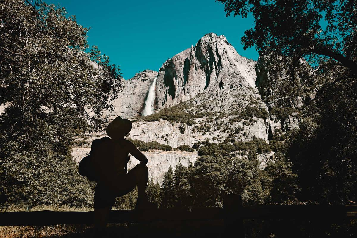 hiker silhouette in front of mountain face with waterfalls