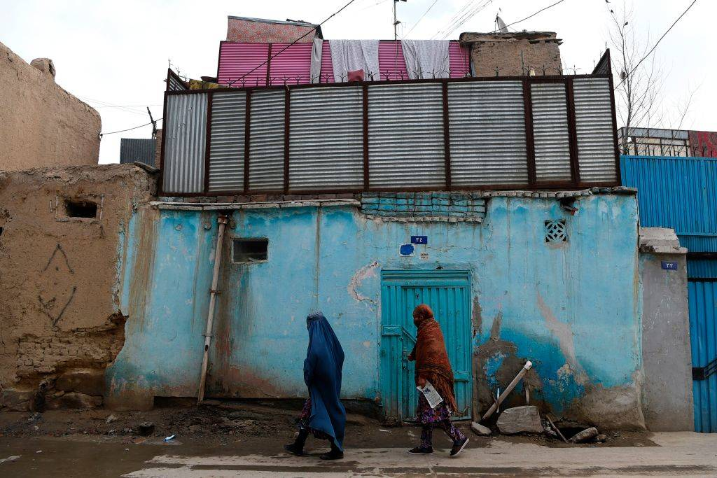 two people walking in a worn down area of Kabul, Afghanistan