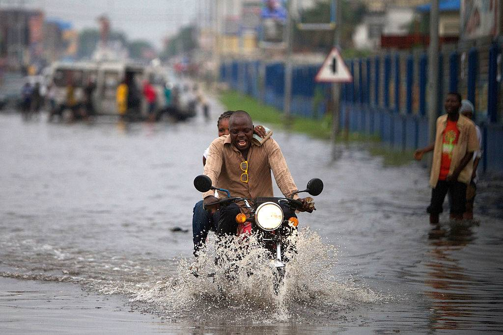 people riding a motorcycle in a flooded street in Kinshasa, The Democratic Republic Of Congo