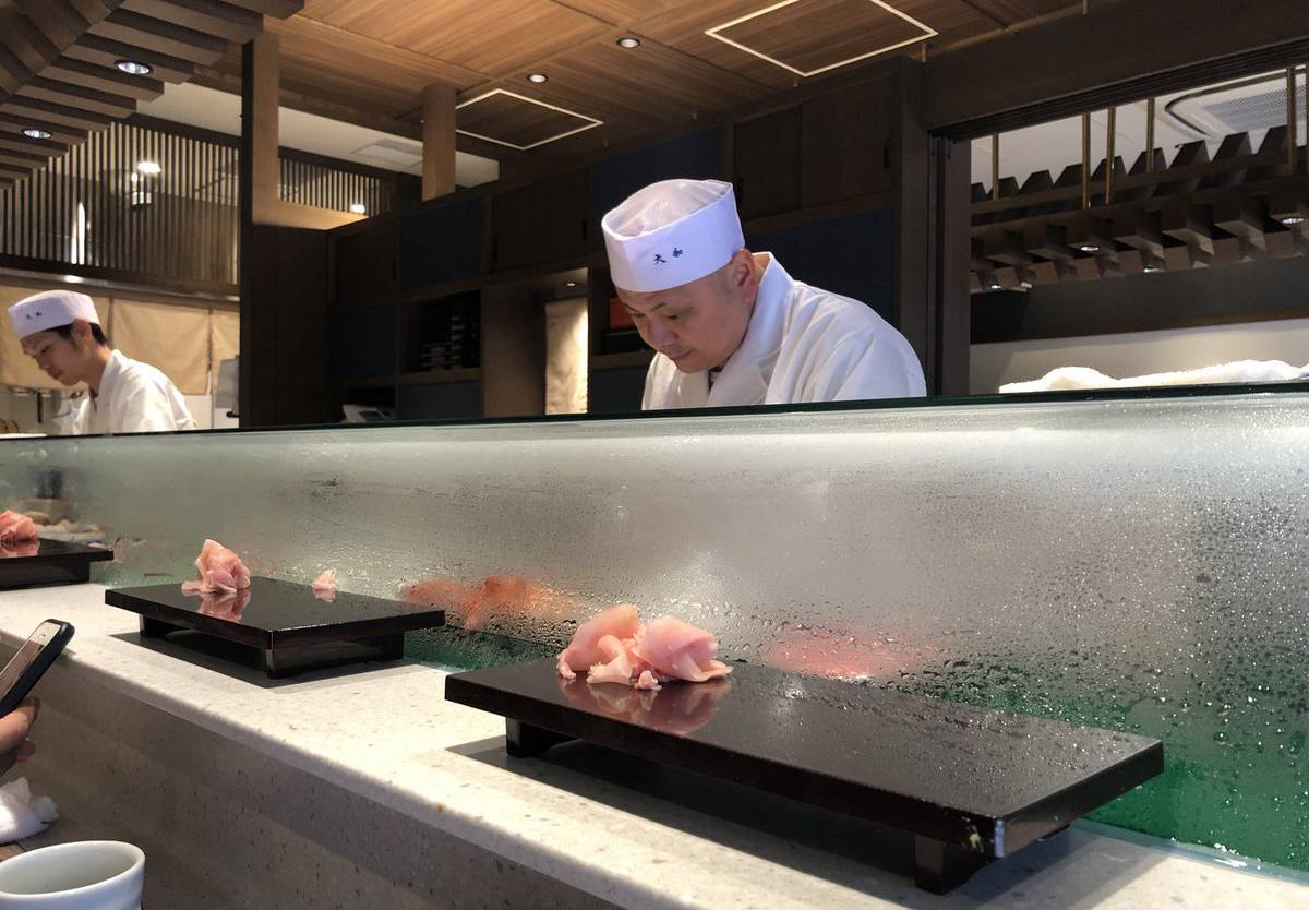 Employees make sushi behind the counter at Sushi Dai.