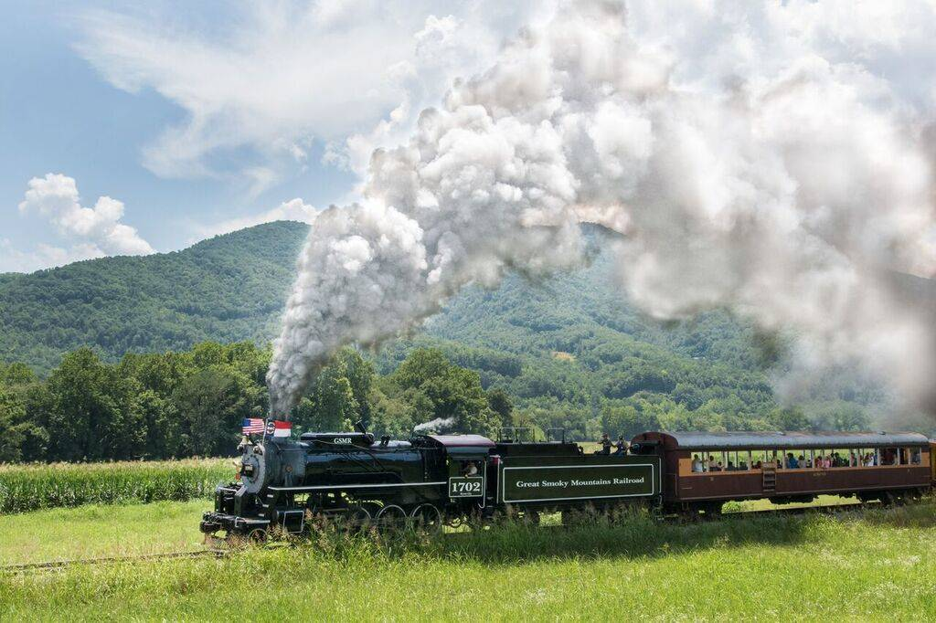 A train releases steam as it rides along the Great Smoky Mountains Railroad.