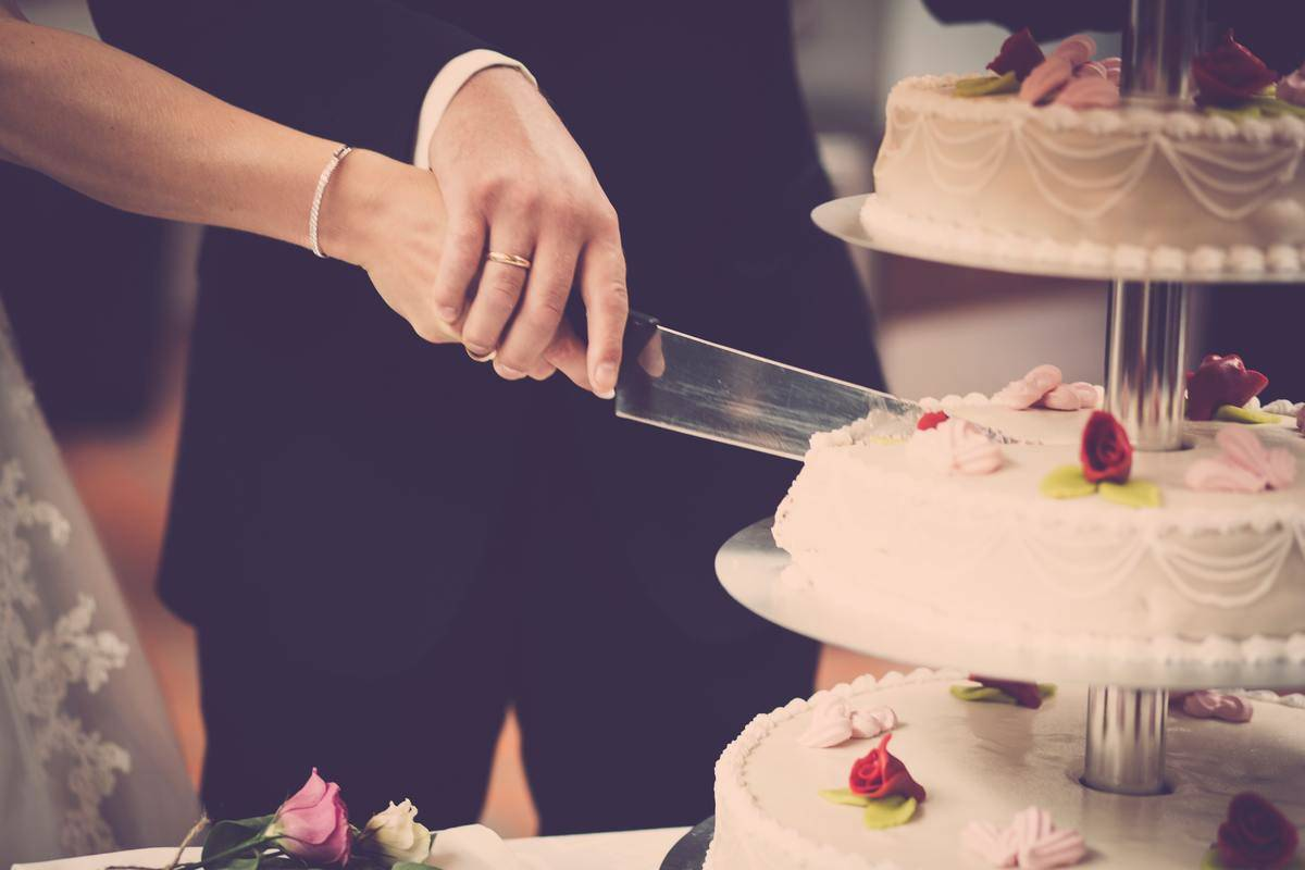 person-holding-knife-slicing-3-layer-cake