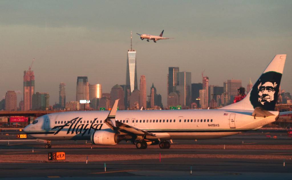 An Alaska Airlines airplane passes by the skyline of lower Manhattan in New York City