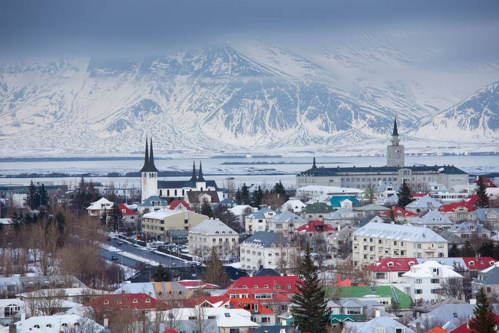 The capital city of Reykjavik, Iceland with traditional bright coloured rooves and snow-covered glacier mountains