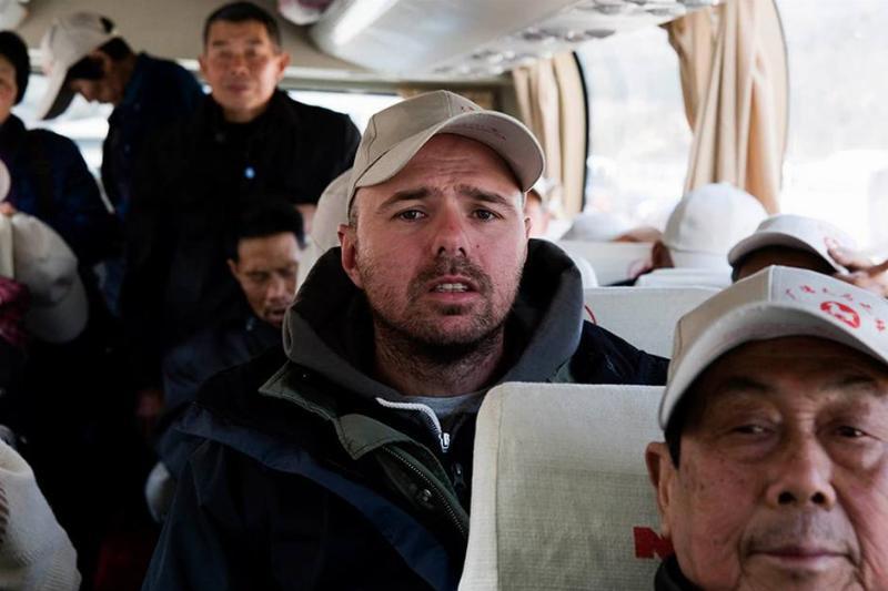 karl pilkington sitting on a bus