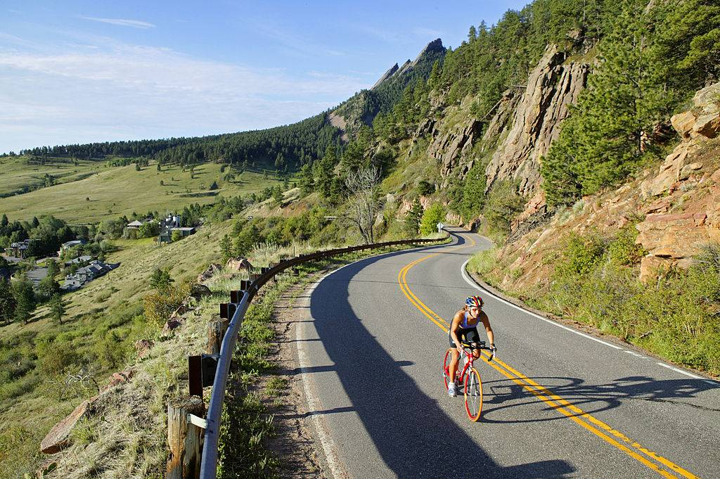 a cyclist on the side of a mountain in boulder, colorado