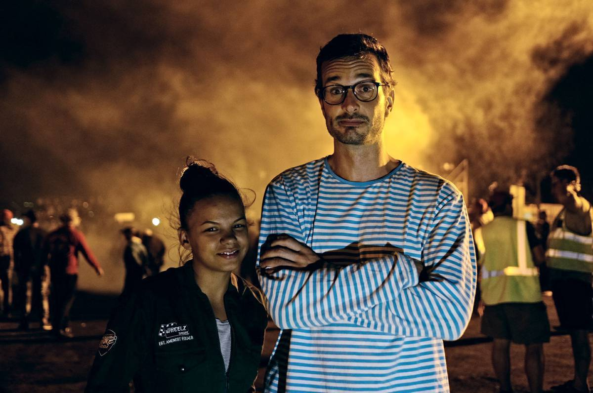 david farrier and stacey-lee may in front of something smoking at night