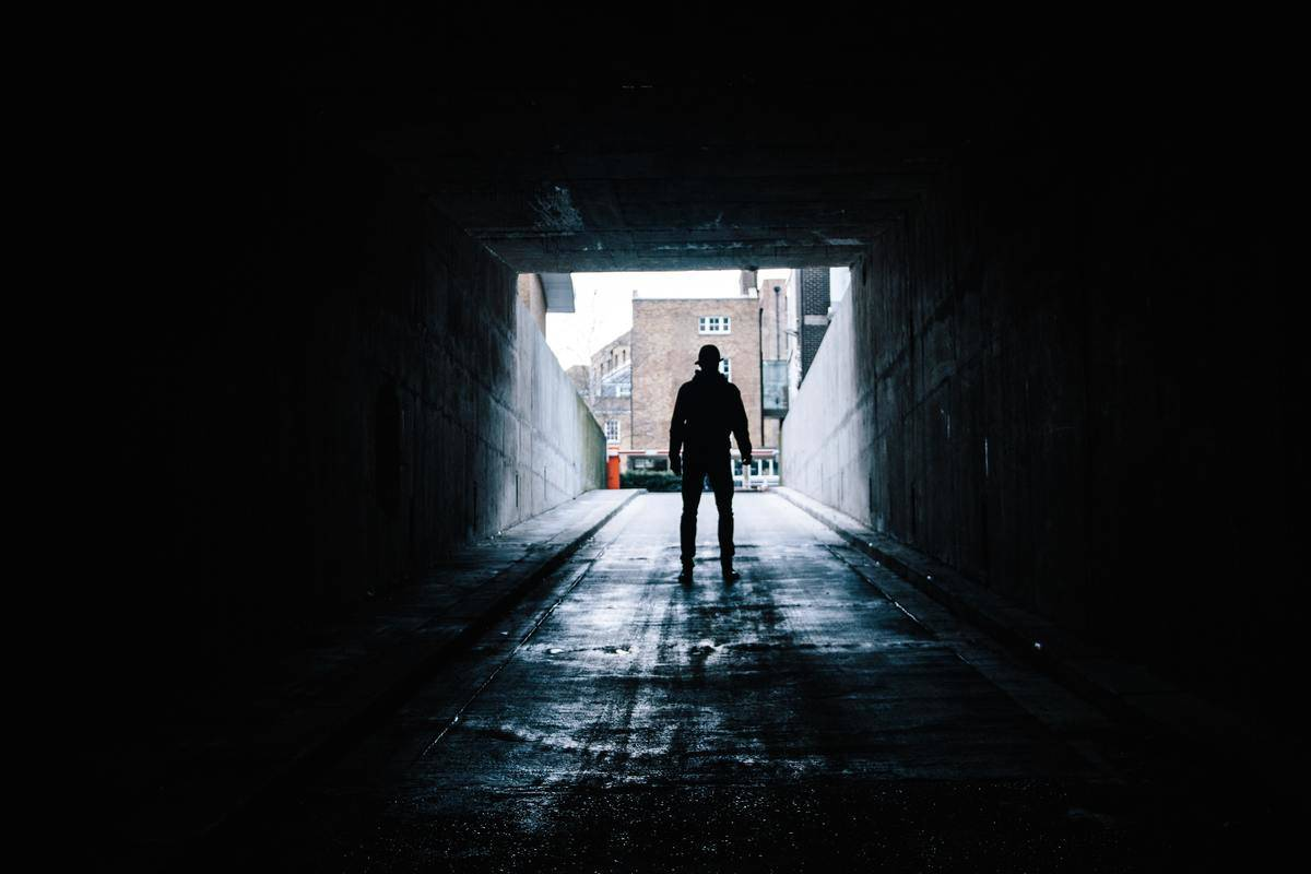 man walking through dark underground tunnel