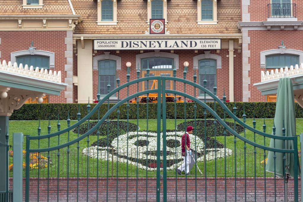 an employee picking up trash at the front gate of disneyland