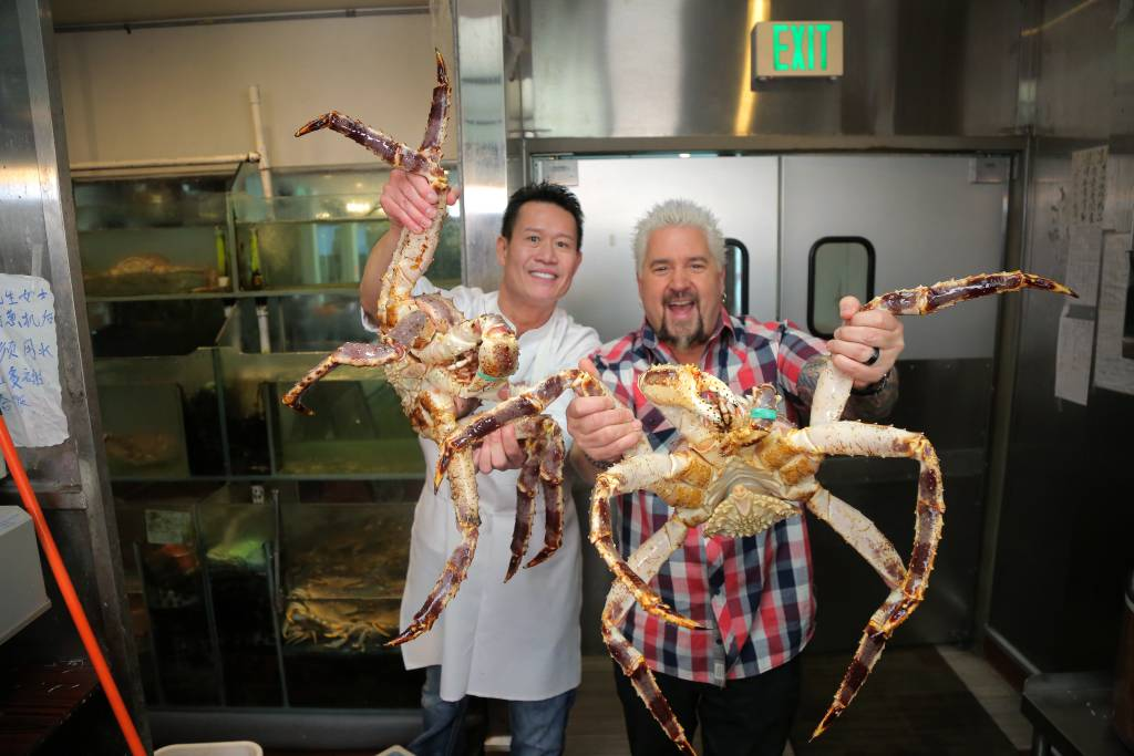 guy fieri and another chef holding up giant crabs