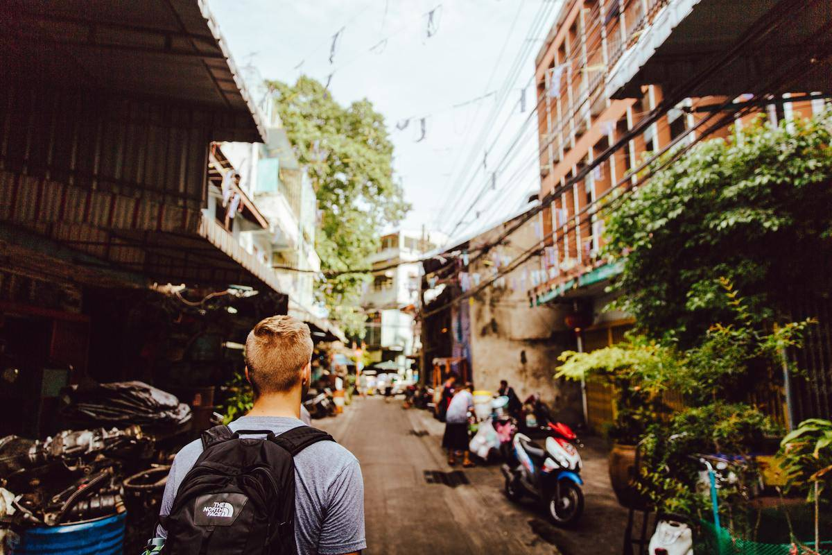 man with backpack walking through back alley in day time