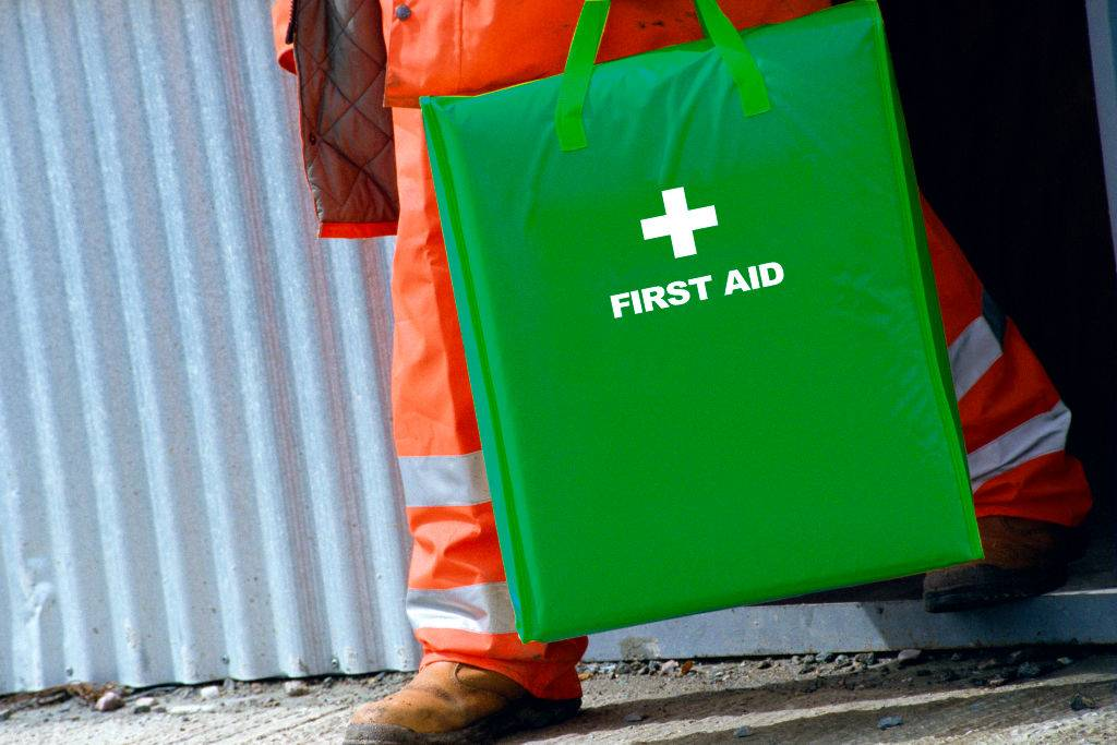 worker holding a green first aid kit