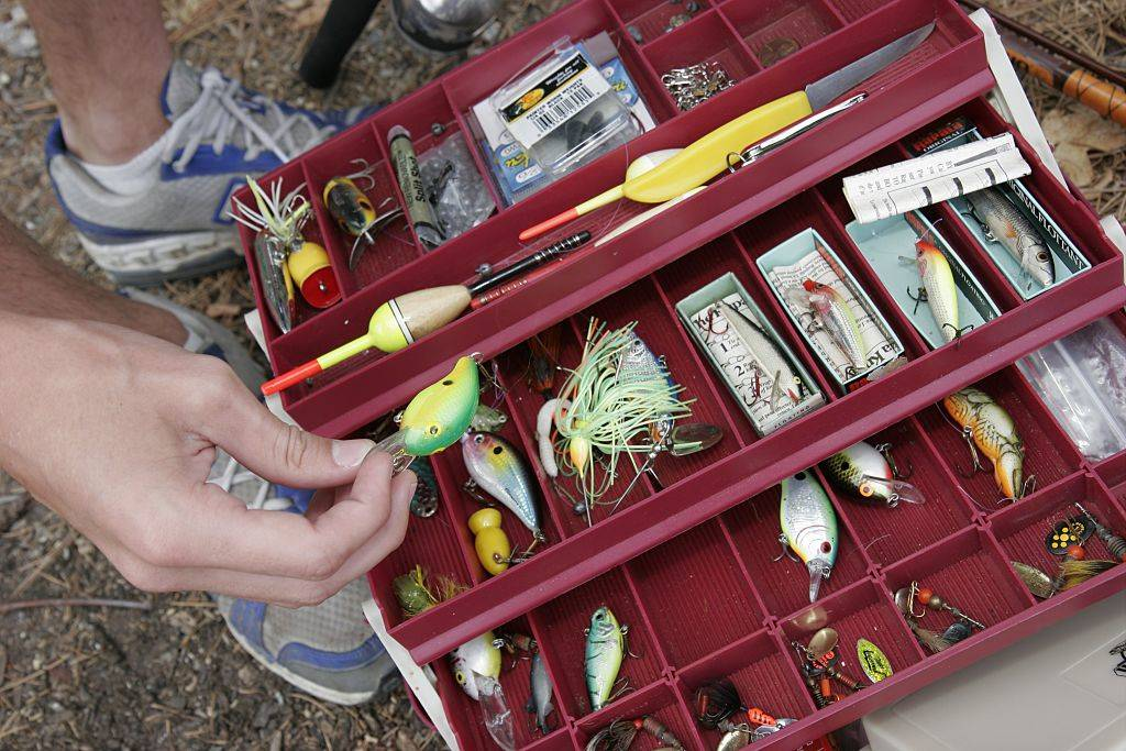 a red bait and tackle box with fishing equipment