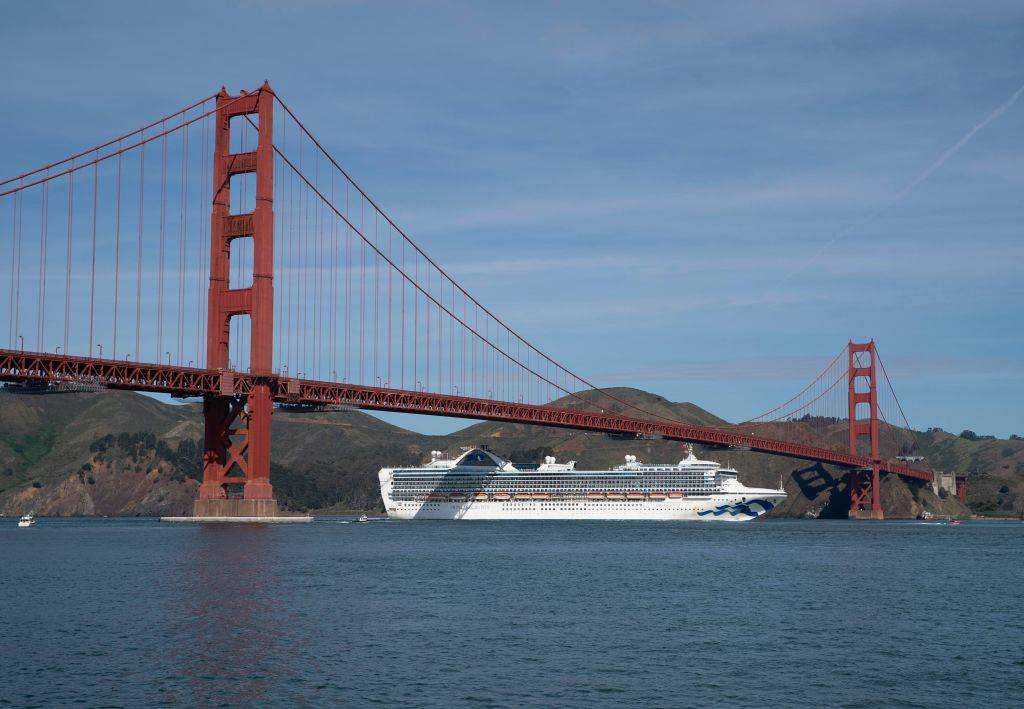 golden gate bridge with a cruise ship underneath in the water