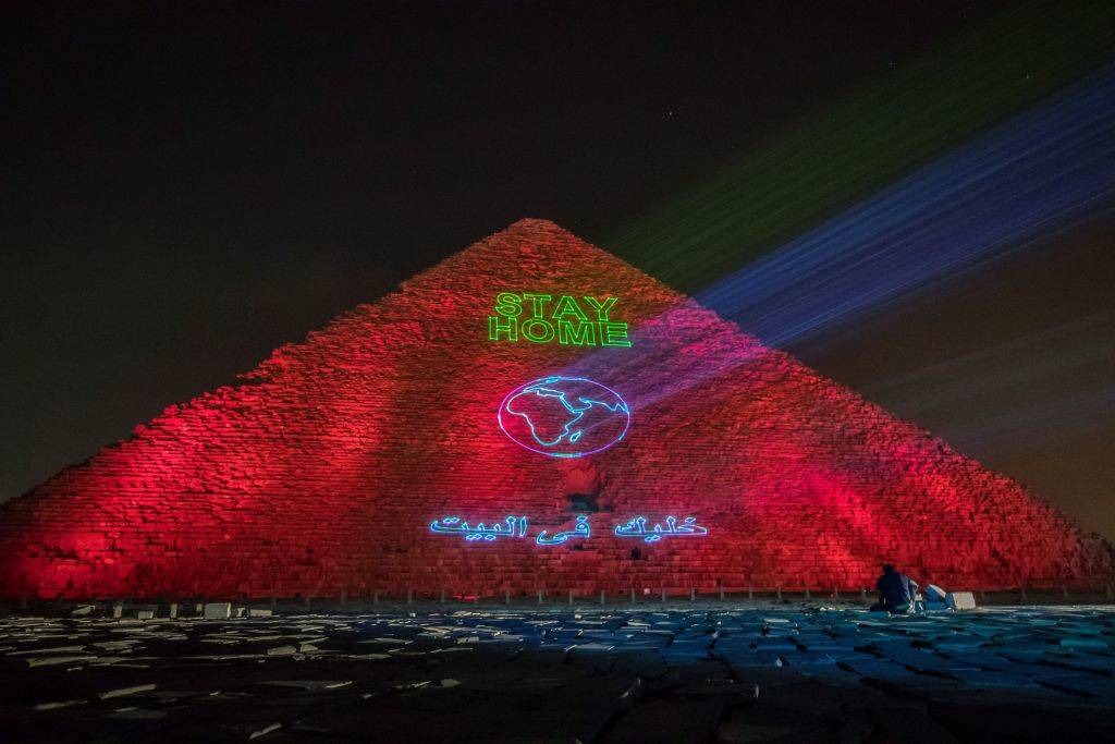 the great pyramid of giza with lights that say stay home