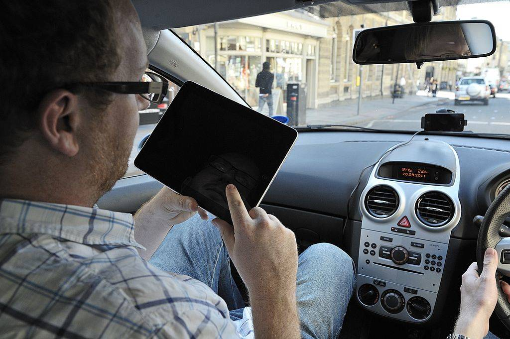 A man using an Apple iPad tablet computer whilst sitting in a car