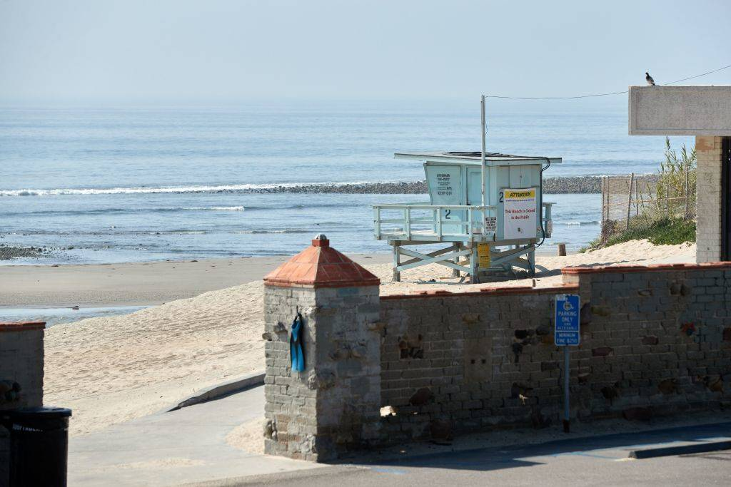 an empty beach in malibu with a lifeguard stand in front of the ocean