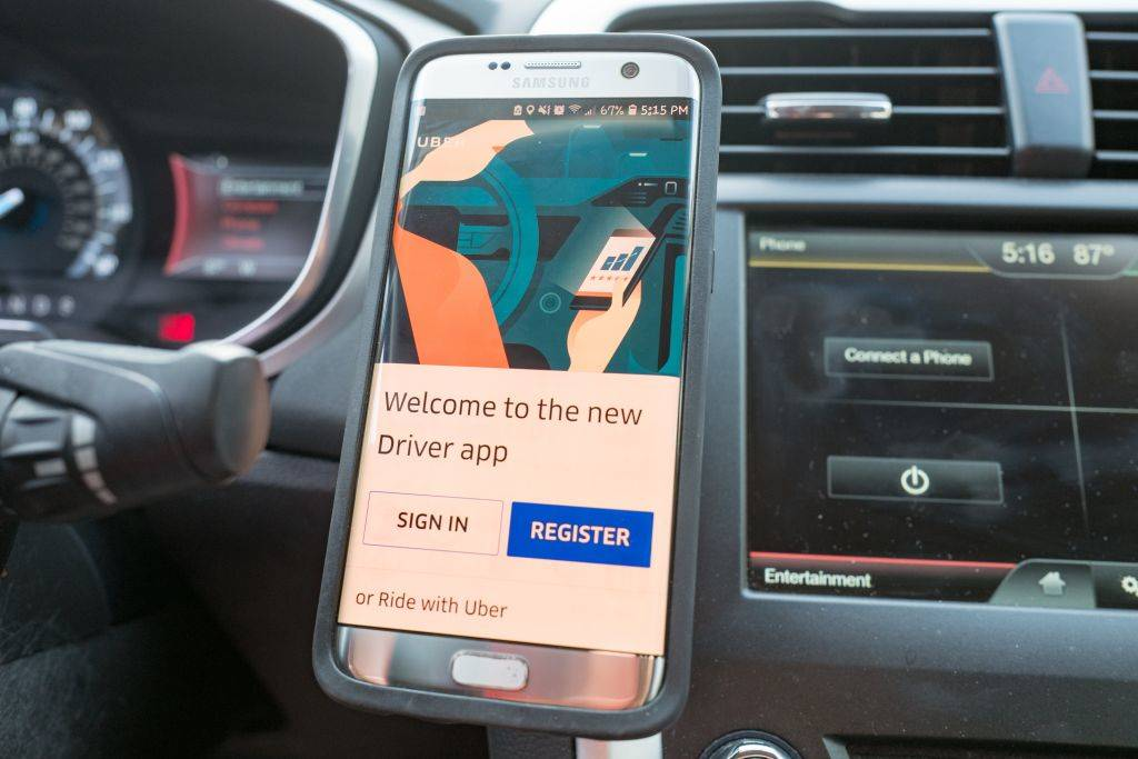 Close-up of a smartphone displaying the Uber driver app installed on a magnetic dash mount