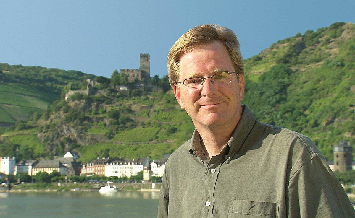 rick steves in front of a castle in europe