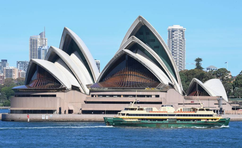 sydney opera house in australia with a boat passing by