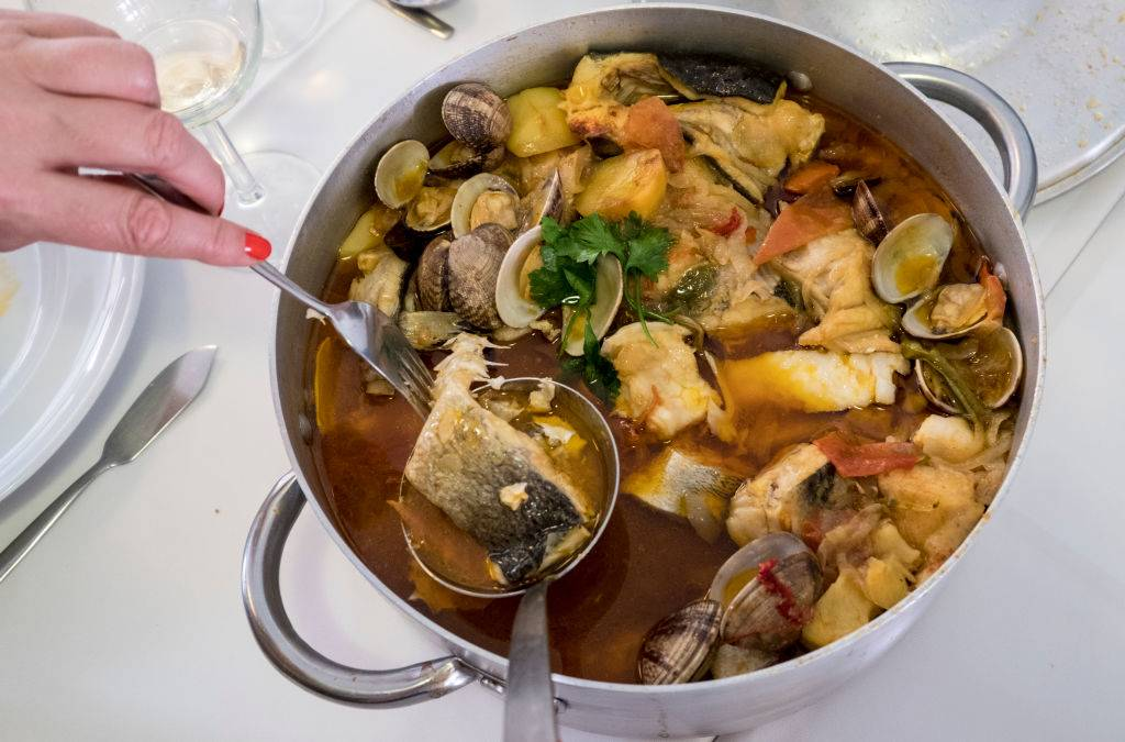 a soup with fish, potatoes, herbs, and seafood