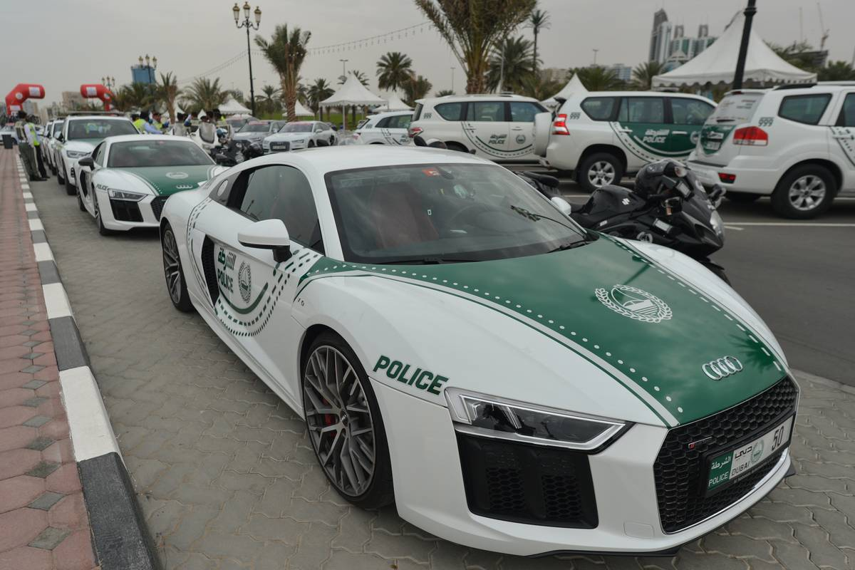 A row of police cars are parked on the street in Dubai.