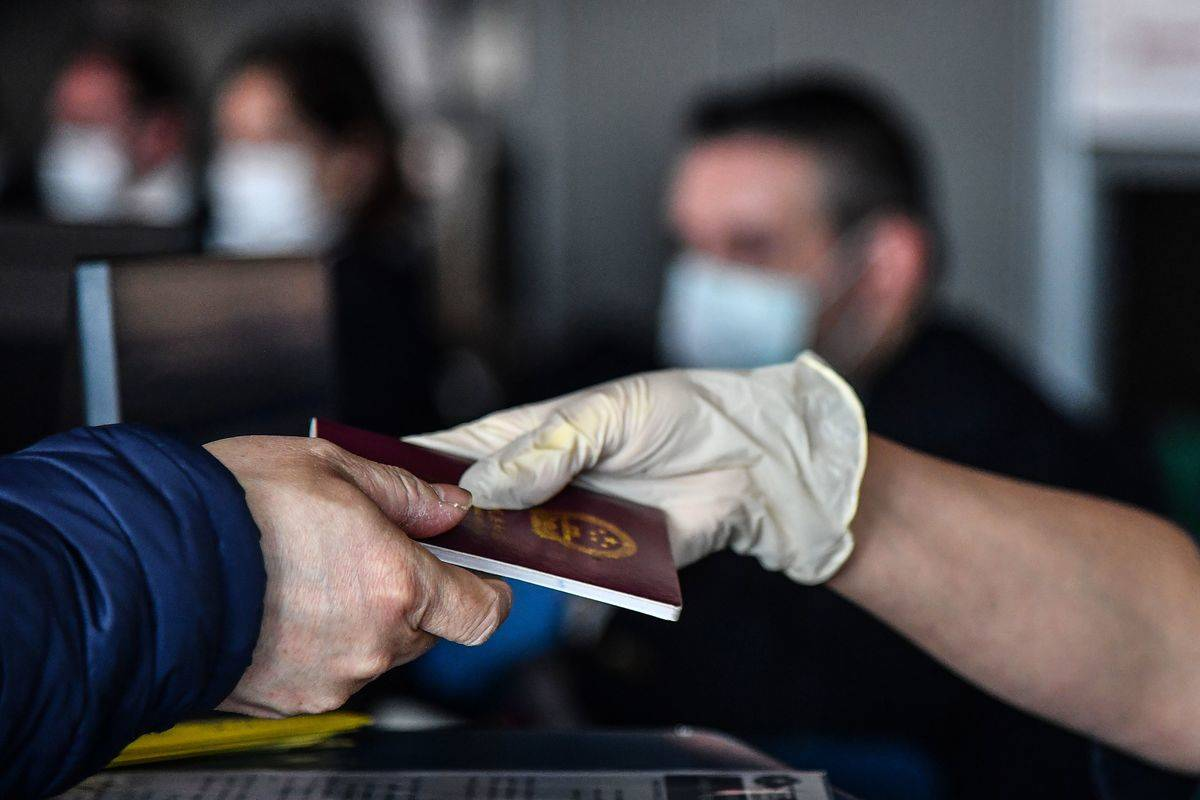 A passenger (L) hands his passport to an employee