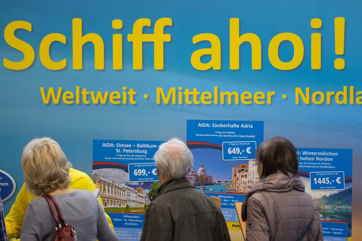 Visitors walk by a billboard for a Dutch cruise ship.