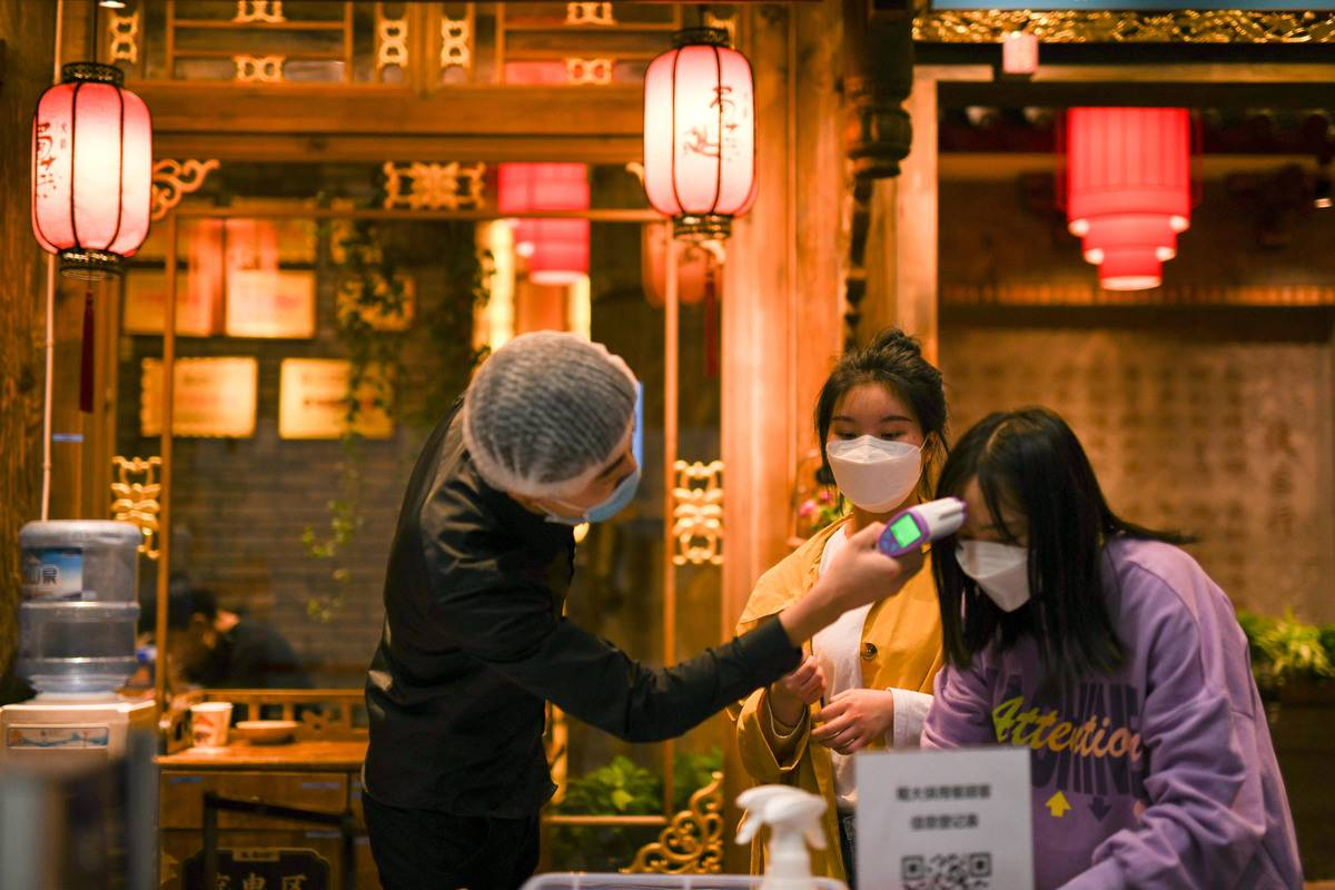 A customer registers as a staff member checks her body temperature at the entrance of a restaurant in Chengdu, southwest China's Sichuan Province