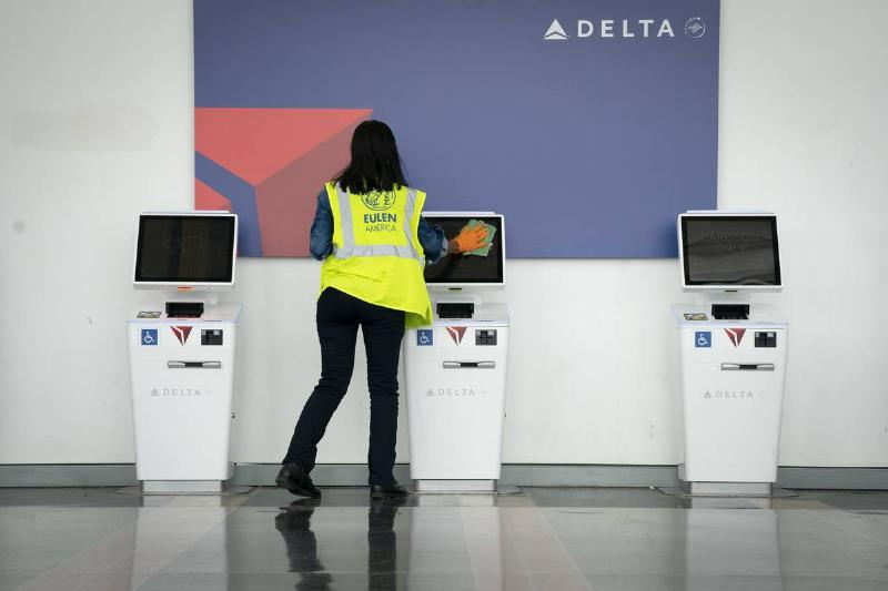 A worker cleans the screens at a Delta self check-in kiosk