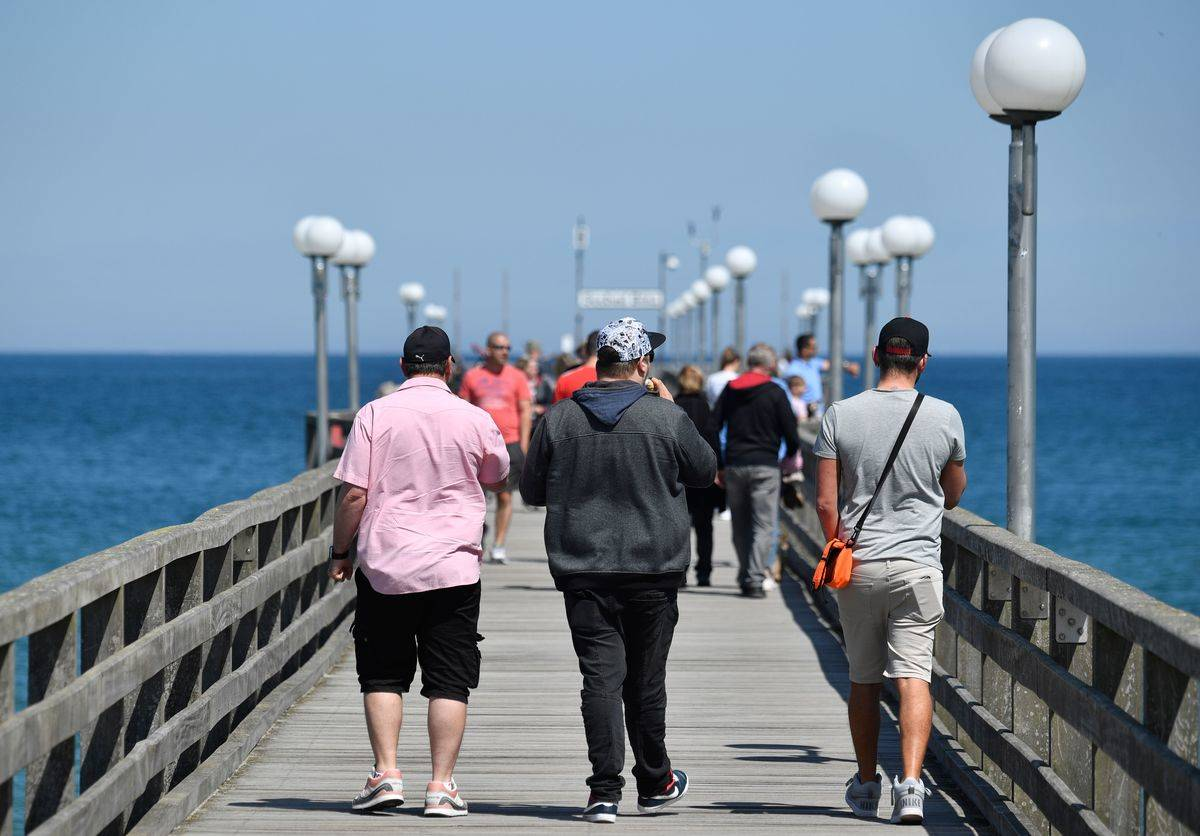 Tourists walk together on a pier in Germany.